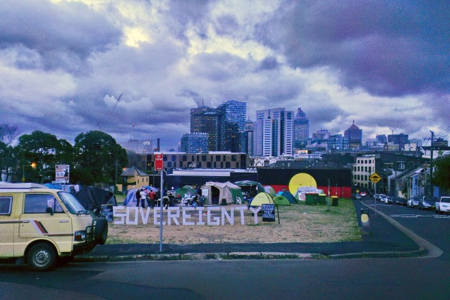 Image Description: The Block, the word sovereignty stands in big letters at front on vacant land where Aboriginal housing once stood. Now occupied by Aboriginal Elders camping in tents to protest commercial development plans. Iconic Aboriginal flag on the wall of the gymn in background. Sydney city rising up behind on the sky line. Lots of dark clouds overhead.