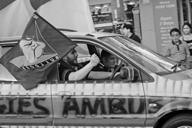 Black and white photograph of Bulldogs fans in a car. The driver is flying a Bulldogs flag out the window as he drives.