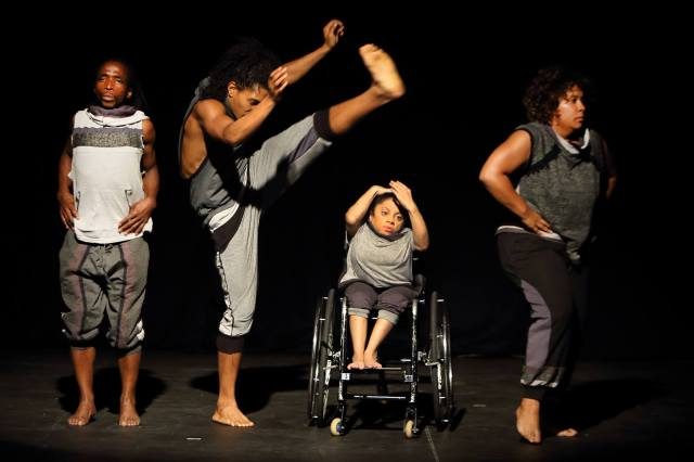 From left to right, two male dancers, one standing facing audience, the second lifting his arms and one leg high over the third dancer who is seated in a wheelchair. She leans away from him and holds her hands on her head. The last dancer, a woman, stands facing the away from the other dancers. They are all dressed in casual pants and tee shirts in various shades of grey.