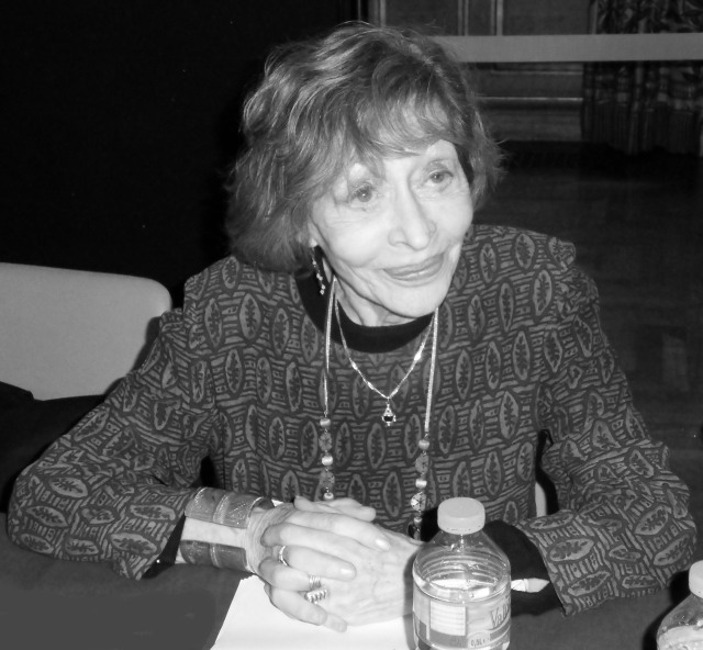 A recent black and white photograph of Alice Cherki, sitting at a table, smiling.