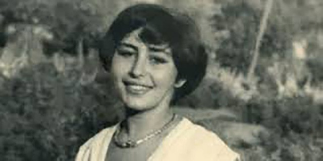 Black and white photograph of Alice Cherki as a young women. She has short, dark hair, is wearing a white, V-neck dress and a necklace, and she is smiling.