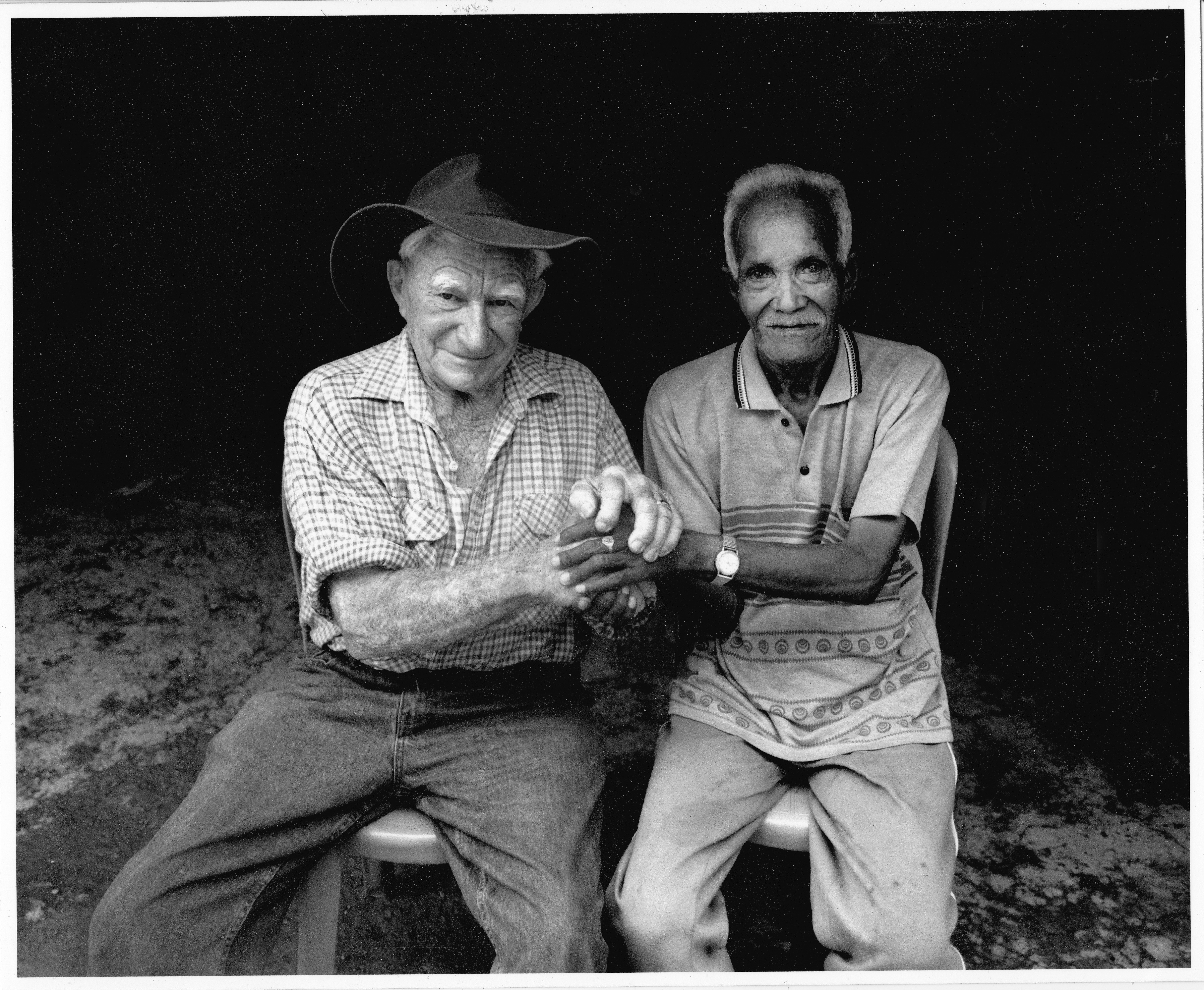 Black and white photograph of World War II veterans, Paddy Keneally and Rufinl Alves seated and holding hands.