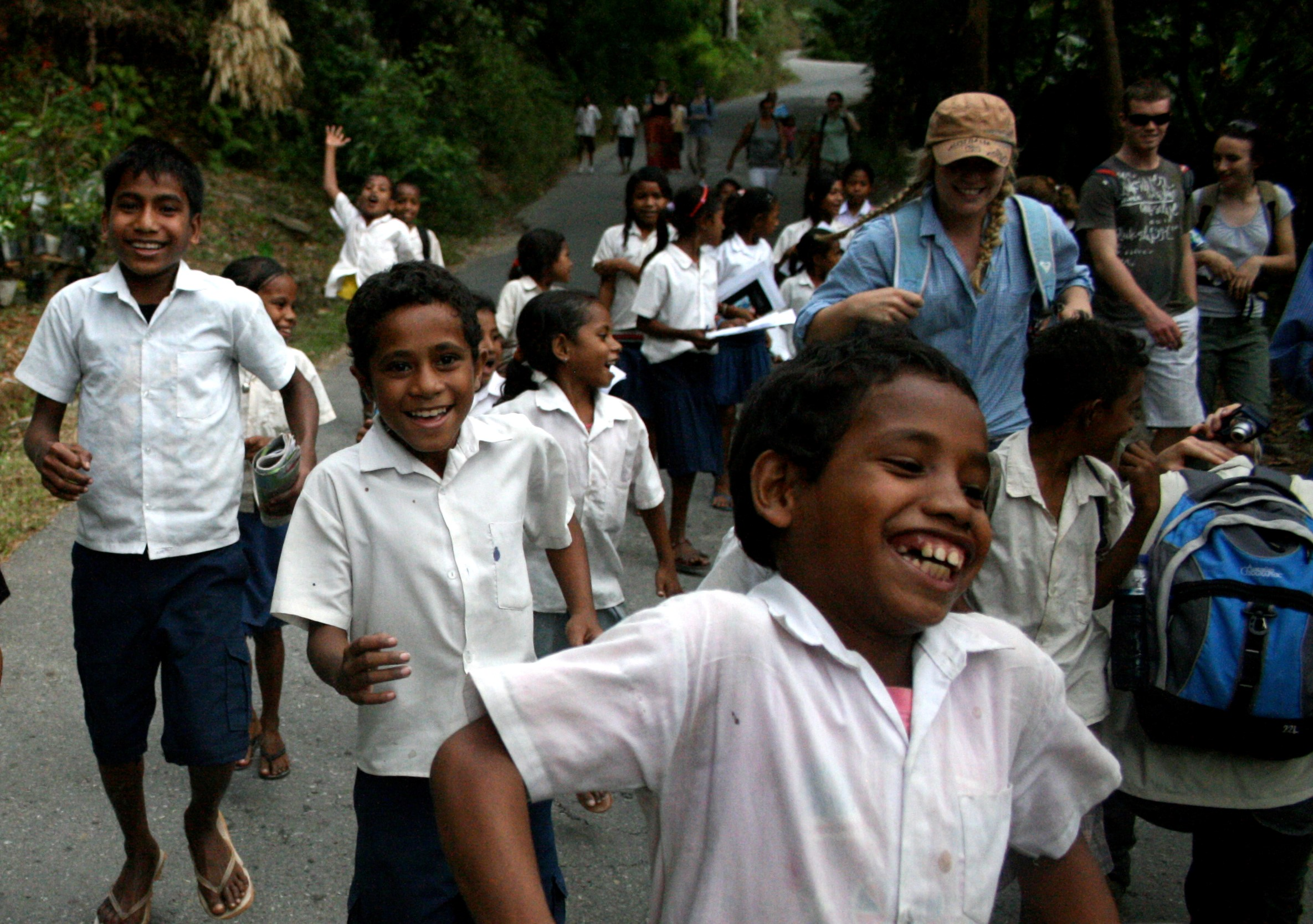 Timorese school children dressed in uniform - white shirts and grey shorts and skirts walkingand running along a road surrounded by greenery. They are having fun. Three Australian college students in their midst.