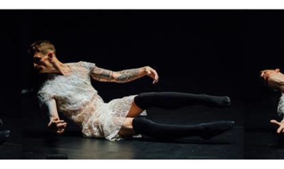 Colour Photograph of Dan Daw performing. He is dressed in a flimsy, short white lace dress and wears black thigh-length stockings. He is partially sitting on a black stage with black background, leaning back, head turned looking at the floor, arms stretched out slight to the front of his body. His legs are raised off the floor. He has short, fair hair and tattoos on his arms.