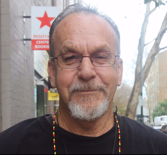 Head shot of Ken Canning. He is wearing glasses, and a long necklace of small, red, gold and black beads (Aboriginal colours). He has a greying mustache and beard, and he is smiling.