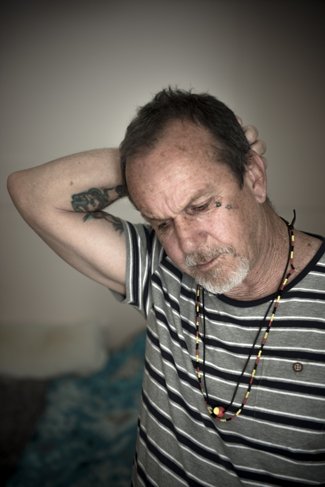 Colour photograph, interior, mid shot of Ken Canning standing in his apartment. Right hand clasped around the back of his head. He wears a striped grey, white and black T-shirt and two necklaces in the colours of the Aboriginal flag.