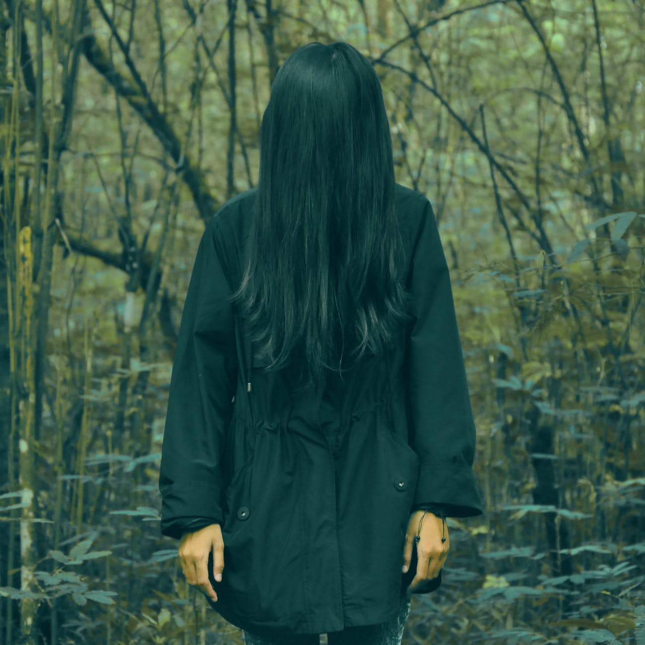 Colour photograph of a woman standing in a black coat in a forest. Her face is completely covered by her long black hair.