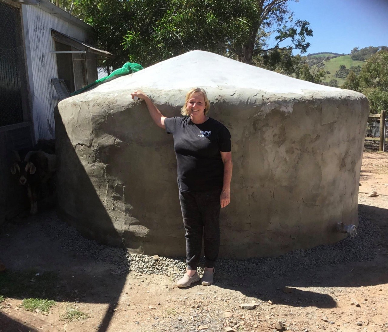 Kerrie Carroll standing in front of the completed earthbag tank