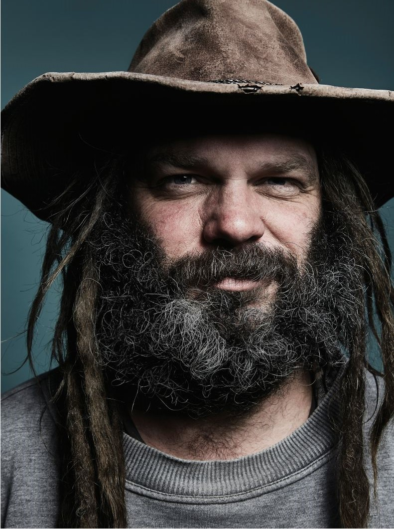 Head shot of Scotty Foster. He has a beard and dreadlocks and is wearing a wide-brimmed, leather hat
